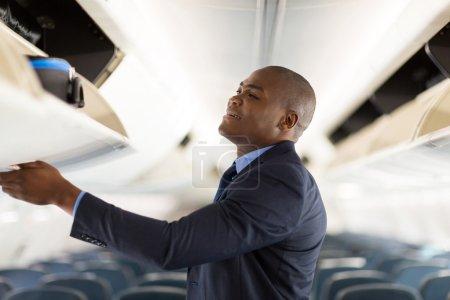 Businessman putting luggage away