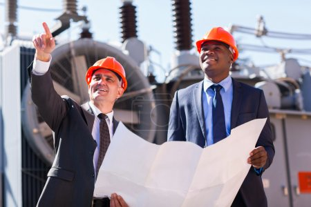 Photo for Power plant managers holding blueprint at substation - Royalty Free Image
