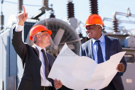 Photo pour Managers discussing blueprint at electrical substation - image libre de droit