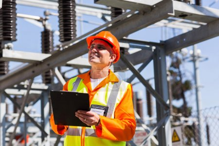 Photo for Handsome middle-aged electrician holding clipboard in electricity power plant - Royalty Free Image