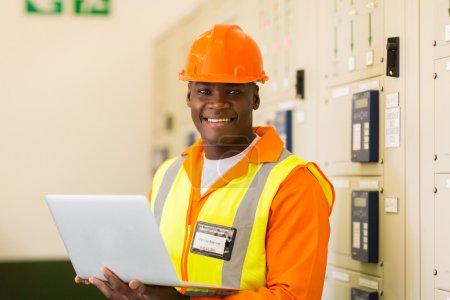Photo pour Verticale d'ordinateur portatif africain de fixation d'ingénieur dans la salle de commande de centrale électrique - image libre de droit