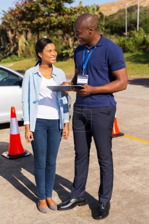 Photo for Beautiful african student driver with instructor filling forms before driving test - Royalty Free Image