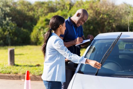 Photo for Female african student driver checking windscreen wiper during a driving test - Royalty Free Image