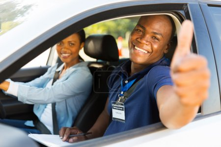 Photo for Happy male african driving instructor in a car with learner driver giving thumb up - Royalty Free Image