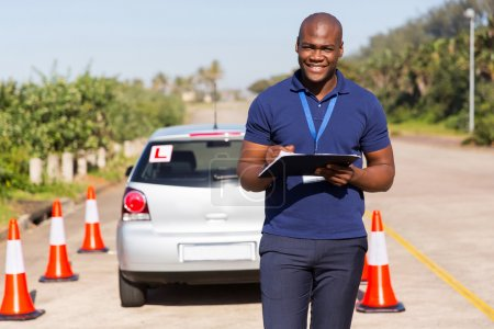 Photo for Portrait of african-american driving instructor writing on clipboard - Royalty Free Image