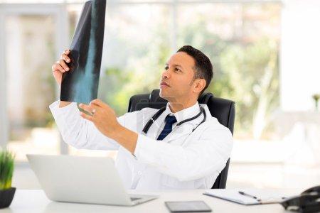 Photo pour Médecin d'âge moyen regardant la radiographie du patient au bureau - image libre de droit