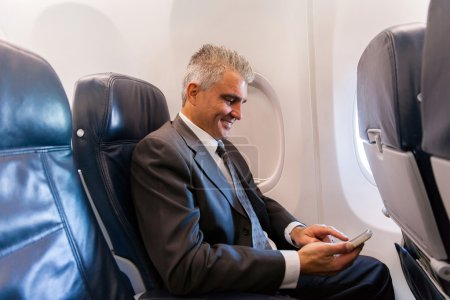 Businessman using cell on airplane