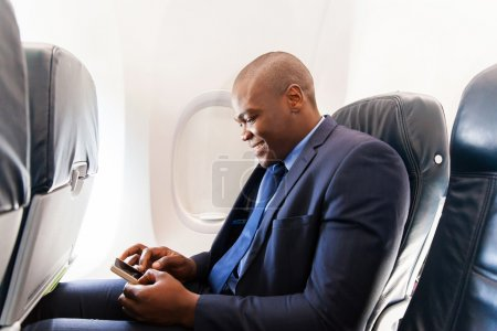 African airplane passenger using smartphone