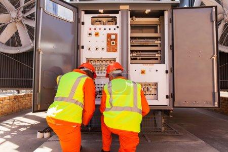 Electricians repairing transformer