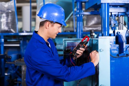 Industrial technician examining control box