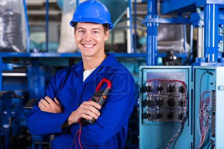Photo for Industrial electrician with crossed arms holding insulation tester in factory - Royalty Free Image