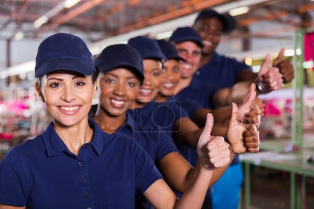 Photo pour Clothing factory workers showing thumb up by hand - image libre de droit