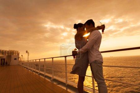 Photo pour Couple romantique étreignant les yeux fermés au coucher du soleil sur un bateau de croisière - image libre de droit