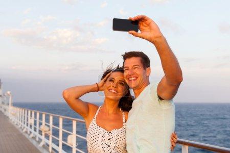 Photo pour Couple joyeux prenant des photos d'eux-mêmes sur un bateau de croisière - image libre de droit