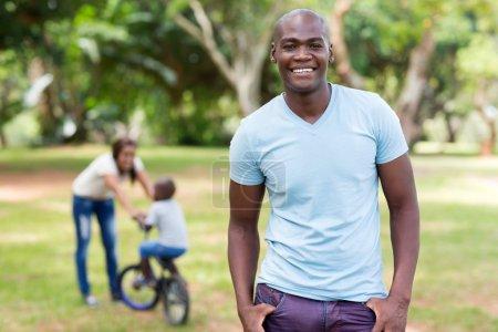 Photo pour Bel homme afro-américain debout devant la famille à l'extérieur - image libre de droit