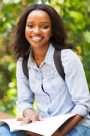 Photo pour Jolie jeune étudiante africaine souriante en plein air - image libre de droit