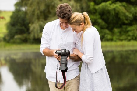 young couple viewing pictures on camera