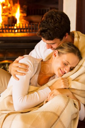 Couple wrapped in blanket at home