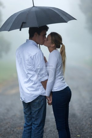 Photo for Boyfriend and girlfriend kissing under umbrella in the rain - Royalty Free Image