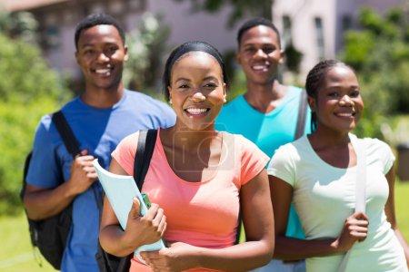 Photo pour Belle fille de collège afro-américaine debout devant des amis - image libre de droit
