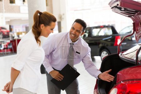 car salesman showing new vehicle to customer