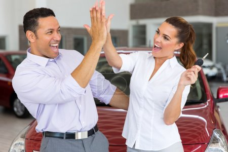 Couple giving high five after buying new car
