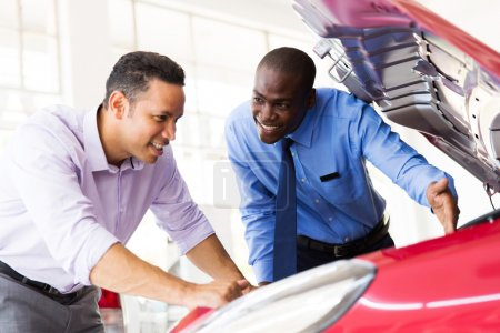 sales consultant and customer looking at a car engine