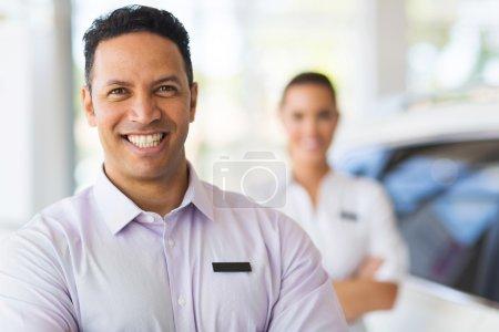 Car salesman standing in front of colleague in sho...
