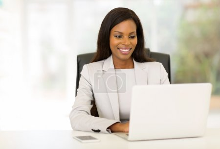 Photo pour Happy afro american businesswoman using computer in office - image libre de droit