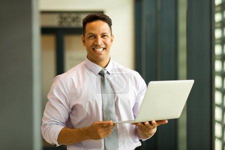 mid age employee holding laptop