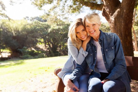 Photo for Attractive mid age mother and daughter sitting on a bench outdoors - Royalty Free Image