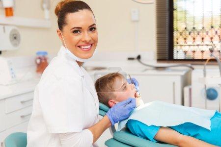 Photo pour Belle jeune dentiste et petite patiente en clinique - image libre de droit