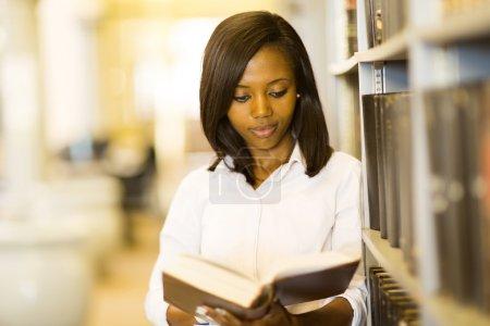 Photo pour Jolie étudiante africaine lisant un livre à la bibliothèque - image libre de droit