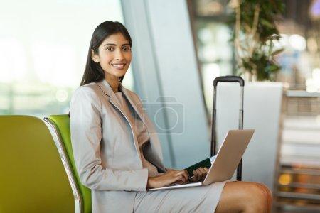 Photo pour Portrait de jeune femme indienne heureuse en attente au salon de l'aéroport - image libre de droit