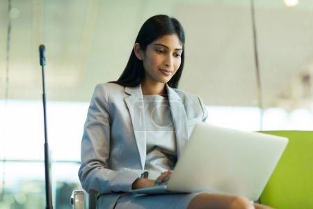 traveler using laptop at airport