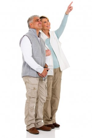 Photo pour Charmant couple de personnes âgées pointant vers l'espace de copie vide sur fond blanc - image libre de droit