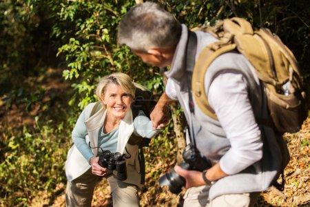 man helping wife climbing mountain