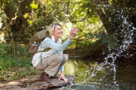 female hiker playing with stream water