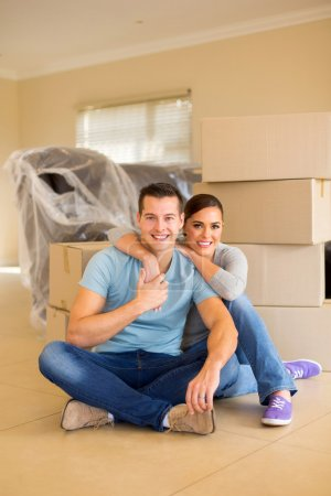 Photo for Lovely couple sitting on floor in new home - Royalty Free Image