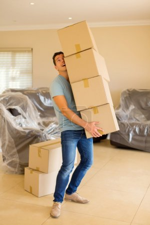 Photo for Young man carrying stack of cardboard boxes at new house - Royalty Free Image