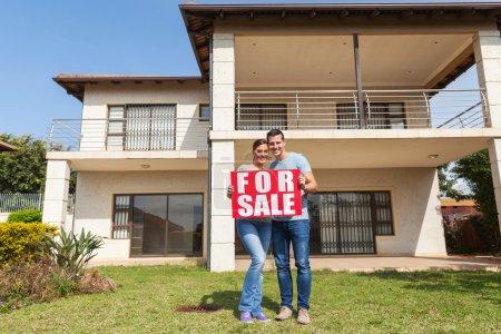 Photo pour Portrait de charmant couple tenant à vendre signe devant la maison - image libre de droit