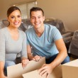 Happy young couple with boxes in new home...