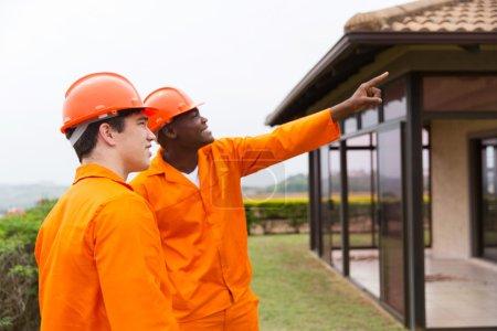 Photo pour Professionnel multiracial hommes travailleurs de la construction pointant vers la maison avant la rénovation - image libre de droit