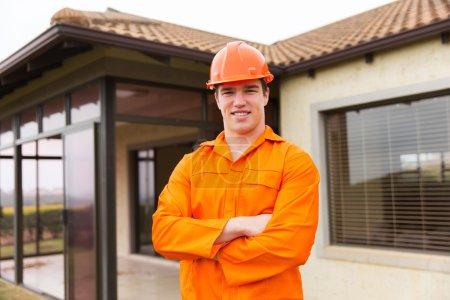 Photo pour Jeune ouvrier de la construction les bras croisés devant une maison - image libre de droit