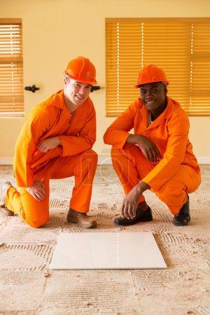 Photo pour Collègues professionnels de la construction discutant carreaux de sol - image libre de droit