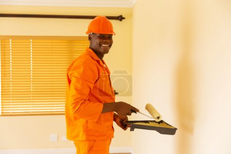 builder holding paint roller and paint