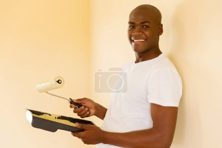 Photo for Handsome african american man painting wall at home - Royalty Free Image