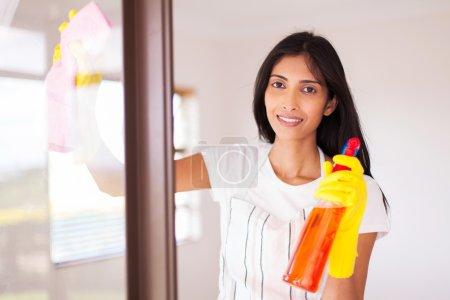 Photo pour Jolie femme au foyer indienne nettoyage vitre - image libre de droit