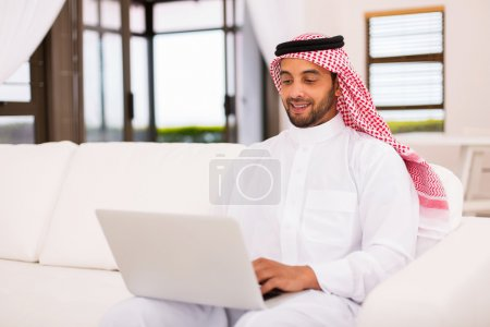 Photo for Young muslim man using laptop at home - Royalty Free Image