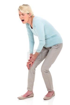 Photo pour Femme âgée moyenne avec une douleur au genou isolée sur fond blanc - image libre de droit